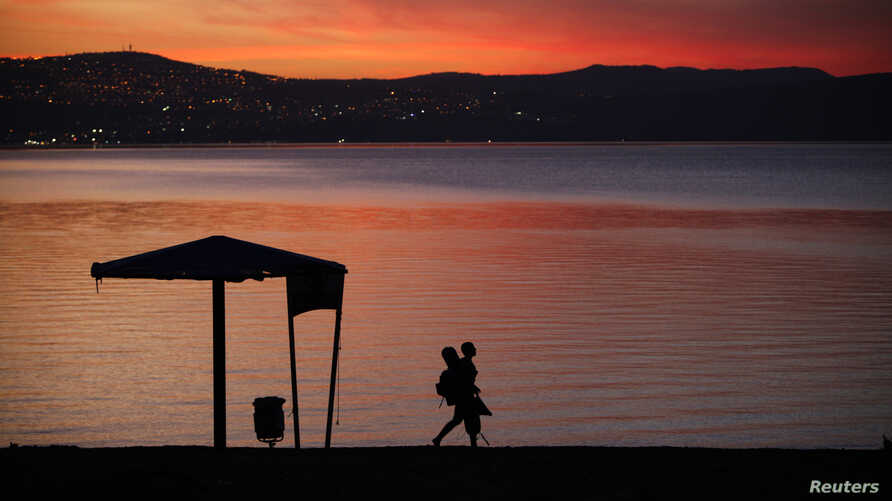 A man walks on the shore of the Sea of Galilee during sunset near the northern city of Tiberias October 29