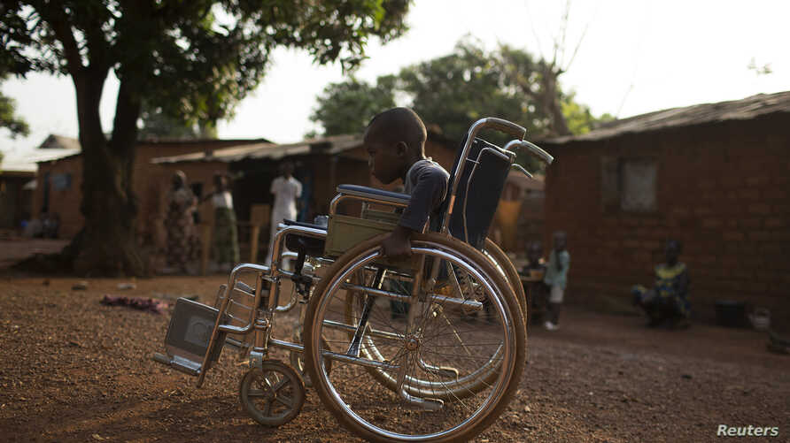 Giovanni Mougounou, 10, who lost both legs in April 2013 to what his family say was a rocket-propelled grenade launched by Seleka fighters on a church, pushes his wheel chair in the Boy Rabe district of Bangui, Central African Republic, February 4, 2