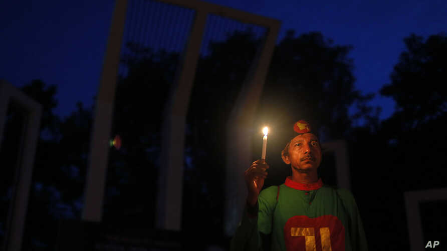 A Bangladeshi activist holds a candle, as they protest against the killing of secular blogger Niladri Chottopadhay Niloy in Dhaka, Bangladesh, Friday, Aug. 14, 2015.