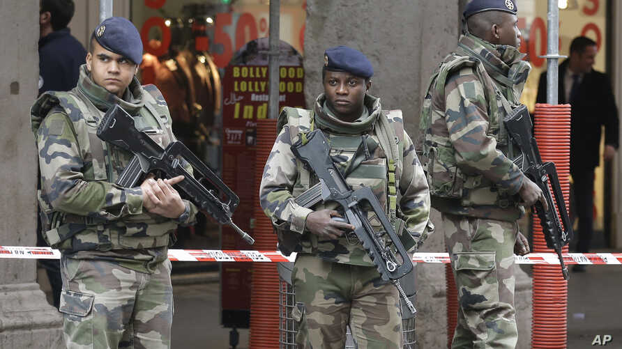 Soldiers stand guard after an attacker with a knife hidden in his bag attacked three soldiers on an anti-terror patrol in front of a Jewish community center in Nice, southern France, Feb. 3, 2015.