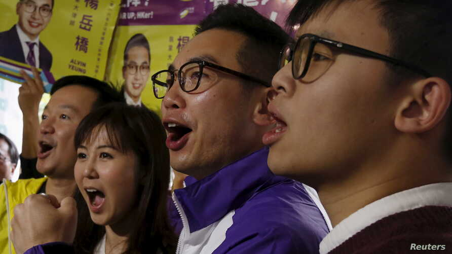 FILE - Alvin Yeung (2nd R), a candidate from Civic Party, chants slogans with supporters at a campaign rally during a legislative by-election in Hong Kong, China.