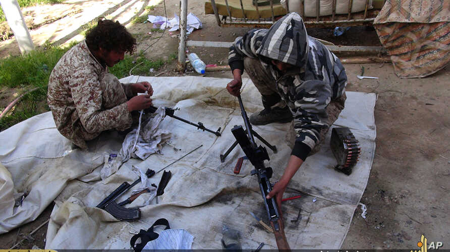 FILE - In this file photo released on June 16, 2015, by Ismamic State militant group supporters on an anonymous photo sharing website, Islamic State militants clean their weapons in Deir el-Zour city, Syria.