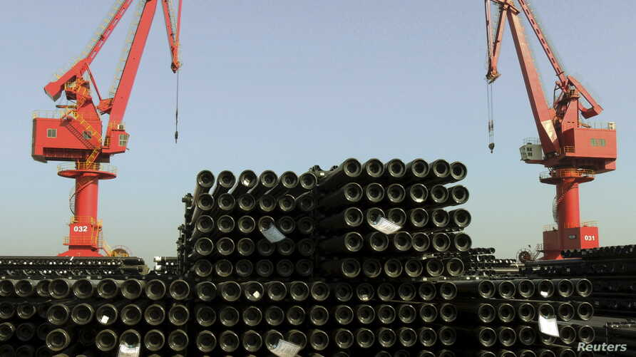 FILE - Cranes are seen above piles of steel pipes to be exported at a port in Lianyungang, Jiangsu province, China, Dec. 1, 2015.