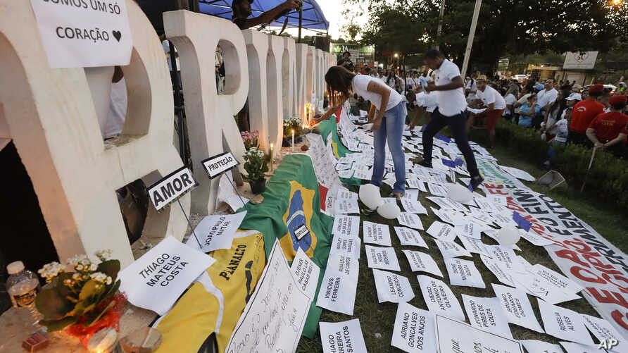 Friends and relatives light candles during a march paying homage to the victims of a mining dam collapse a week ago, in Brumadinho, Brazil, Feb. 1, 2019.