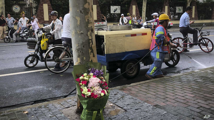 FILE - Flowers left for the victims in a school knife attack in Shanghai, China, June 28, 2018. Thursday a car plowed through a crowd of children outside a primary school, killing five and injuring 18.
