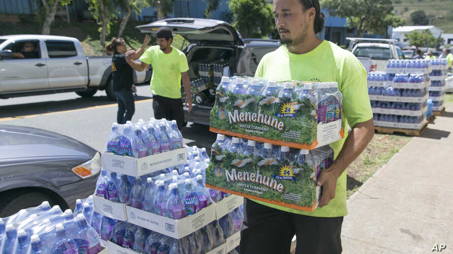 FILE - A worker at the Hawaiian water company carries bottle of water to customers hoping to stockpile water before a 2014 tropical storm.