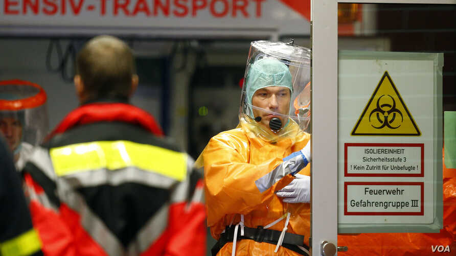 Medical staff members wearing sealed protective suits work during the arrival of an Ebola patient at the Universitaetsklinikum Frankfurt (University Hospital Frankfurt) in Frankfurt, Oct. 3, 2014.