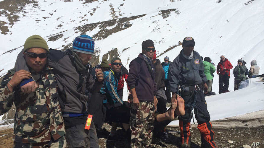 Nepalese army, rescue team members carry avalanche victims to safety at Thorong La pass area in Nepal, Oct. 17, 2014.
