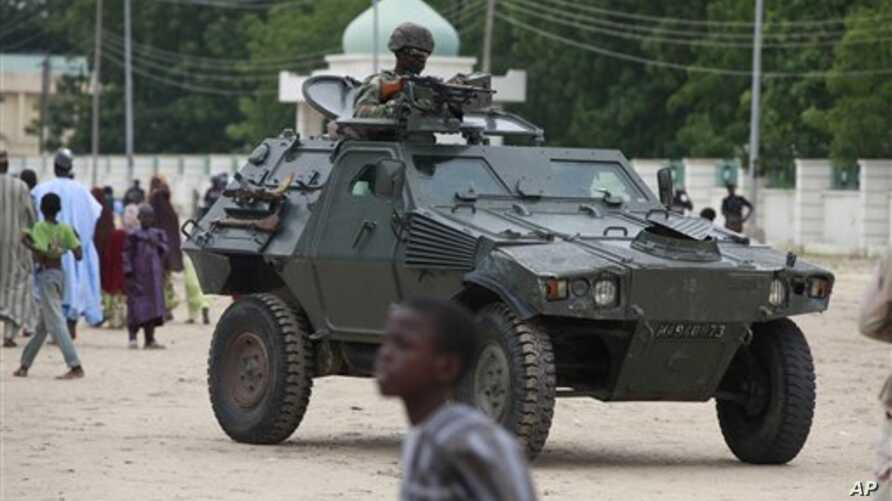 Nigerian soldiers ride on an armored personnel carrier during Eid al-Fitr celebrations in an area of Nigeria where an Islamic insurgency is raging, in Maiduguri, Nigeria, Aug. 8, 2013.