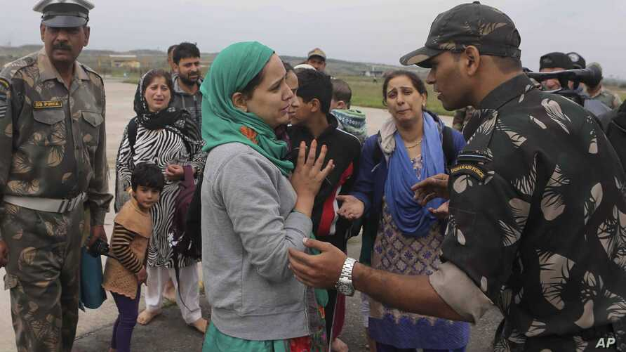A Kashmiri flood victim, center, pleads to an Indian army officer to rescue her family members after she was airlifted by the army from her flooded neighborhood to the Indian Air Force base in Srinagar, Sept. 8, 2014.