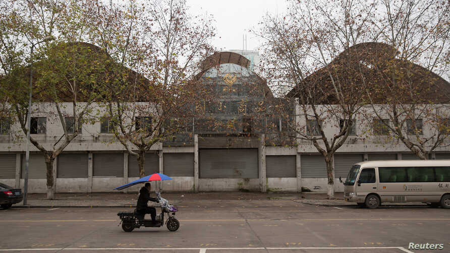 A motorcycle passes a closed-down warehouse in Yiwu, Zhejiang Province, China January 19, 2017.  Picture taken January 19, 2017.