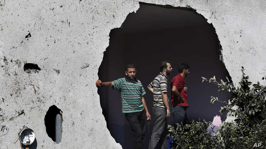 Palestinians, standing under a damaged wall of an adjacent building, watch rescuers searching for bodies and survivors under the rubble of an apartment building, destroyed by an Israeli missile strike, in Gaza City, Monday, July 21, 2014. A woman was...
