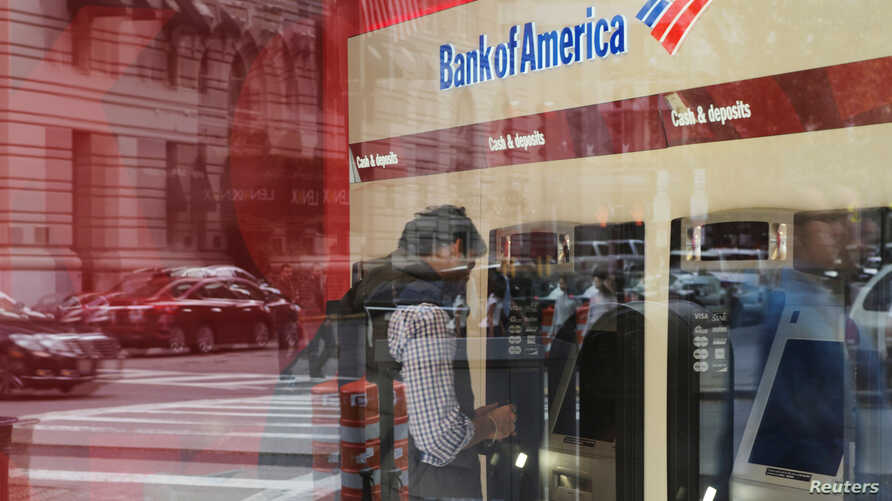 FILE - A customer uses an ATM at a Bank of America branch in Boston, Massachusetts, U.S.