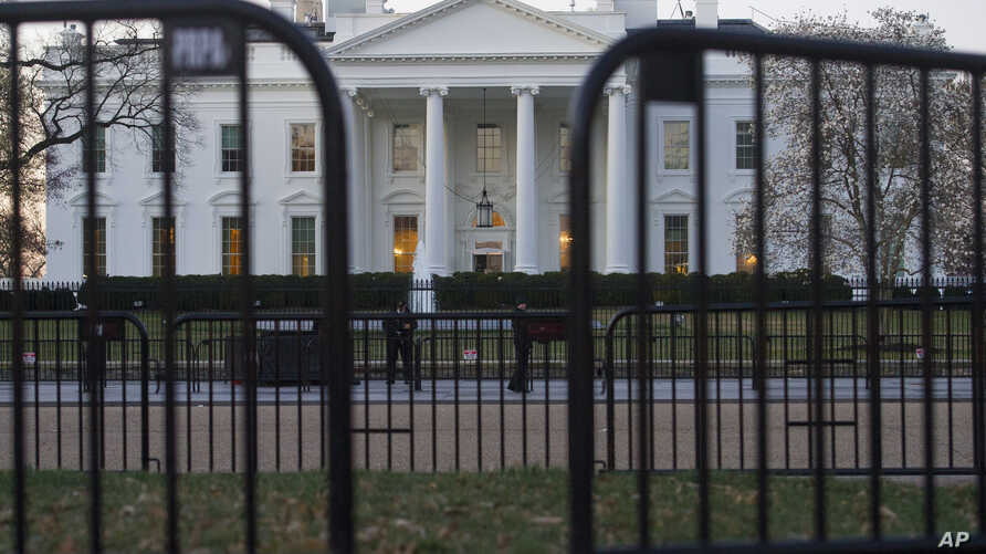 In this March 24, 2019 photo, The White House is seen behind security barriers in Washington. A White House official turned whistleblower says dozens of people in President Donald Trump's administration were granted access to classified information d