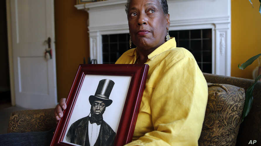 Ocea Thomas poses with a portrait of her ancestor, Samuel Burris, a free black man convicted of helping slaves escape in the 19th century. She reportedly has been told to expect a pardon for Burris, who died in 1863.