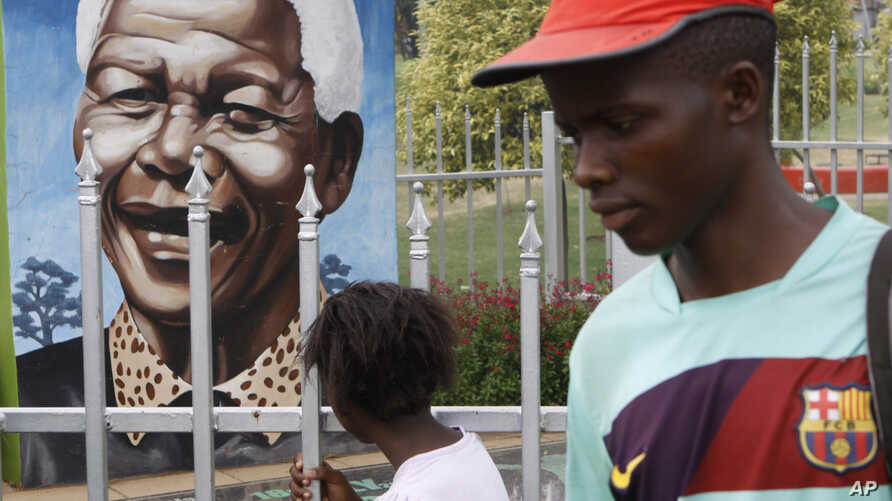 A child looks through a fence at a portrait of former president Nelson Mandela in a Park in Soweto, South Africa, March, 28, 2013.