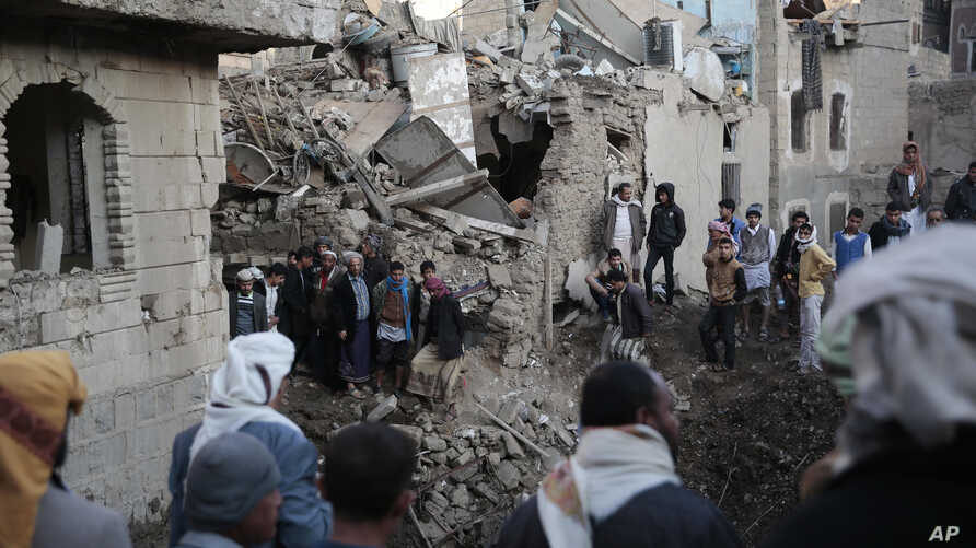 People gather at the site of a Saudi-led airstrike near Yemen's Defense Ministry complex in Sanaa, Yemen, Saturday, Nov. 11, 2017.