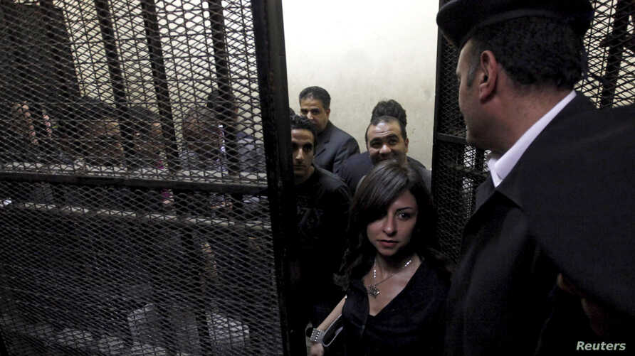 Activists, accused of working for unlicensed non-governmental organizations (NGOs) and receiving illegal foreign funds, stand in a cage during the opening of their trial in Cairo March 8, 2012. Egypt's parliament approved a bill to regulate non-gover
