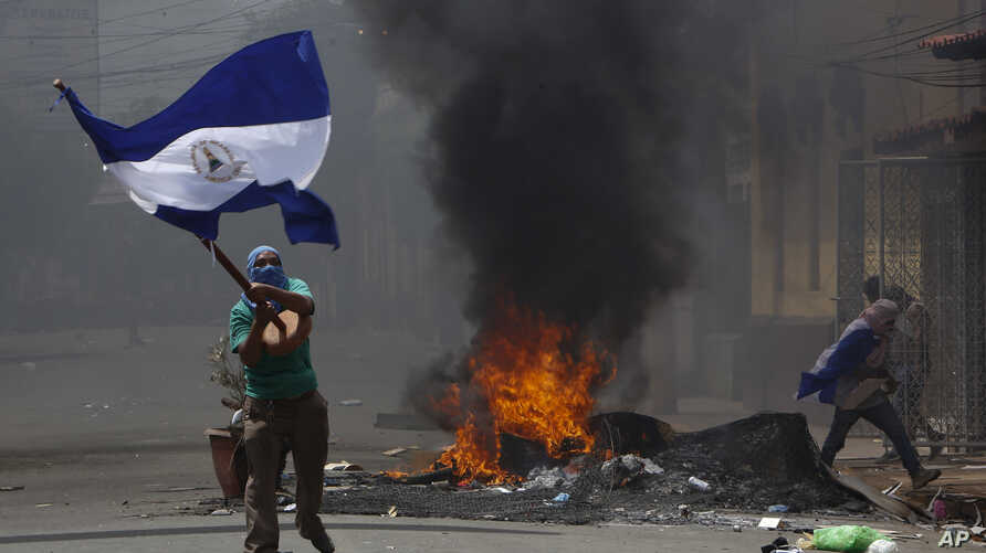 A masked protester waves a Nicaraguan national flag in front of a burning barricade, as protesters clashed with riot police in the Monimbo district of Masaya, Nicaragua, May 12, 2018.