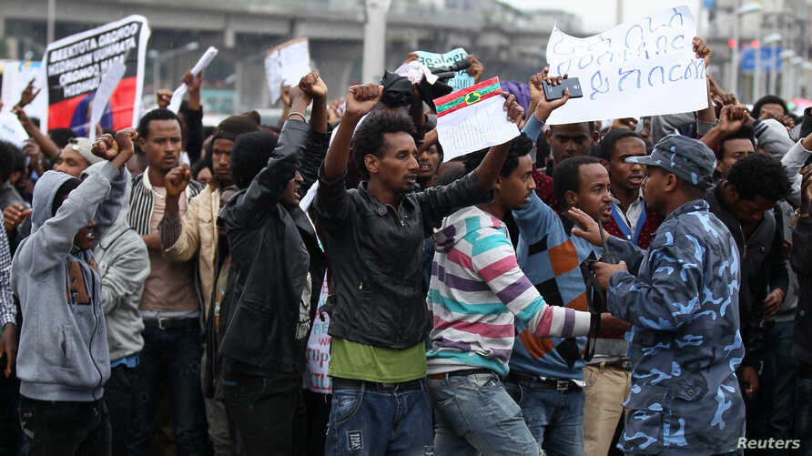 A policeman attempts to control protesters chanting slogans during a demonstration over what they say is unfair distribution of wealth in the country at Meskel Square in Ethiopia's capital Addis Ababa, Aug. 6, 2016.