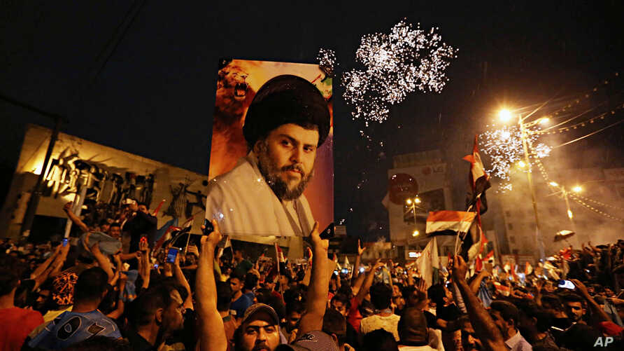 FILE - In this Monday, May 14, 2018 file photo, supporters of Shiite cleric Muqtada al-Sadr, carry his image as they celebrate in Tahrir Square, Baghdad, Iraq.
