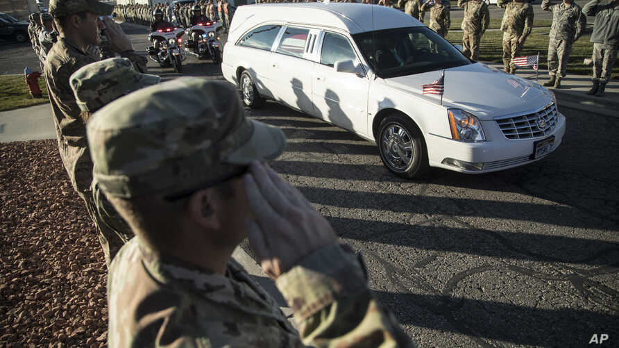 FILE - Utah National Guard members salute as a hearse containing the remains of Maj. Brent Taylor is escorted out of the National Guard base, Salt Lake City, Nov. 14, 2018.