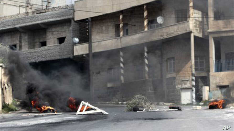 Burning tires and scattered roadblocks set by the anti-Syrian government protesters litter a street, following clashes between the security forces and protesters, in the southern city of Daraa, March 23, 2011