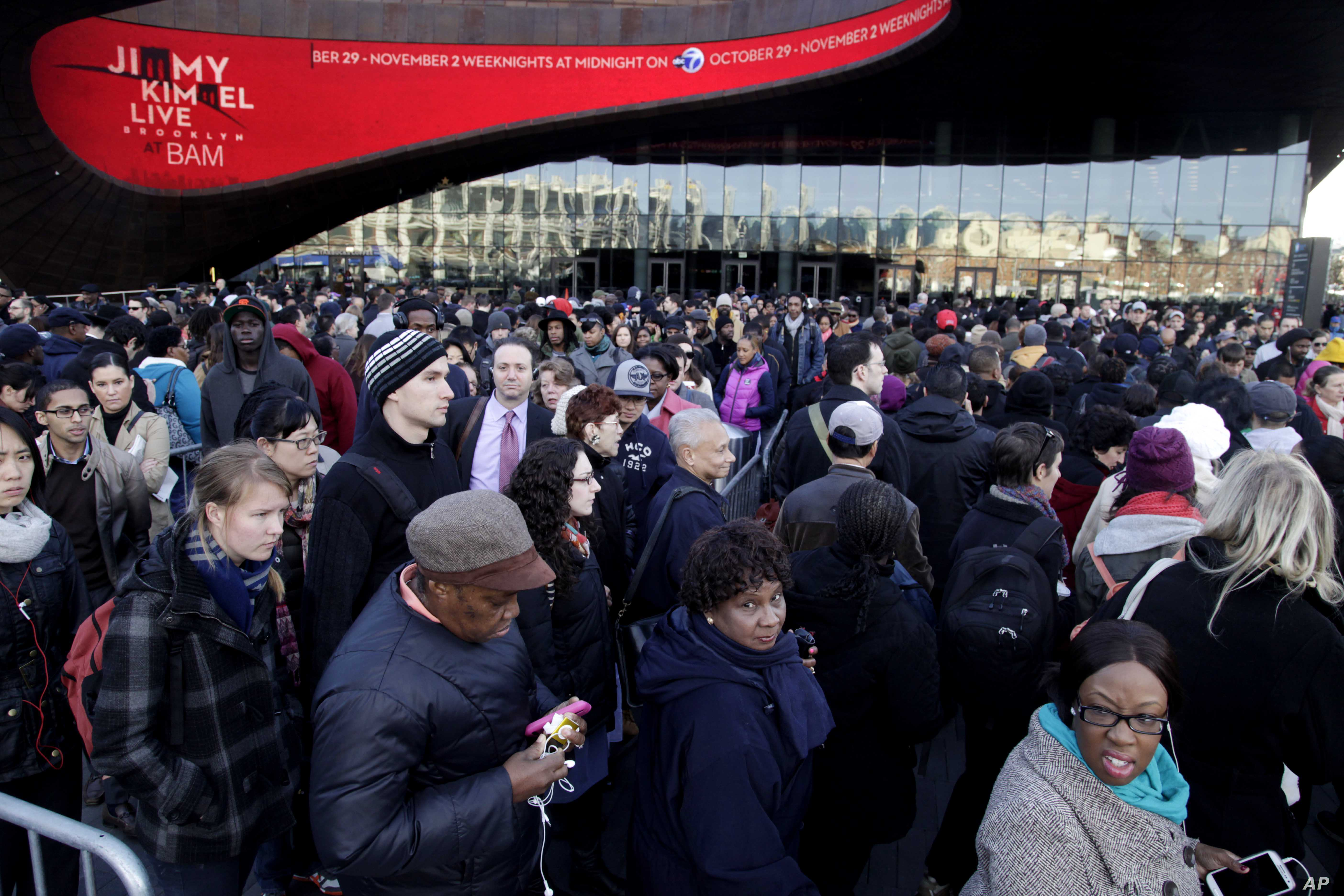Commuters wait in a line to board busses into Manhattan in front of the Barclays Center in Brooklyn, New York,  Nov. 1, 2012.