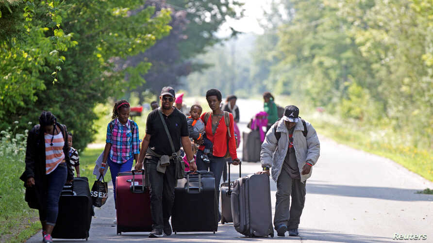 Three families, who said they were from Burundi, awaiting the outcome of their US asylum application by fearing deportation, head to Canada to seek asylum there, Aug. 3, 2017, Champlain, N.Y.