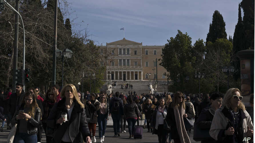 FILE - People walk in front of the Greek Parliament, in central Athens, Jan. 28, 2019.