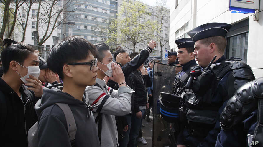 Demonstrators from the Asian community face riot police officers outside Paris' 19th district's police station, Tuesday March 28, 2017.