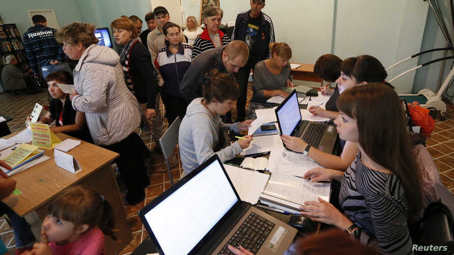 People, who have fled the fighting in the eastern regions of Ukraine, queue for job vacancies at an employment fair at the dormitories where they have taken refuge in Krasnoyarsk Russia, Sept. 2, 2014.