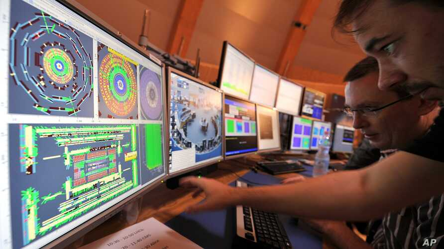 European scientists control computer screens showing traces on Atlas experiment of the first protons injected in the Large Hadron Collider (LHC) during its switch on operation at the Cern's press center on Wednesday, Sept. 10, 2008 near Geneva, Switz