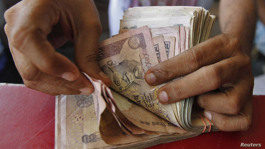 A grocery shop owner counts rupees notes in the western Indian city of Ahmedabad May 23, 2012.