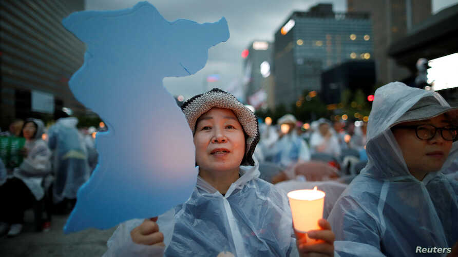 A woman holds a blue-colored cutout of the Korean Peninsula, symbolizing the unification of the two Koreas, during a candlelight vigil wishing for a successful summit between the U.S. and North Korea, in front of the U.S. embassy in Seoul, South Kore...