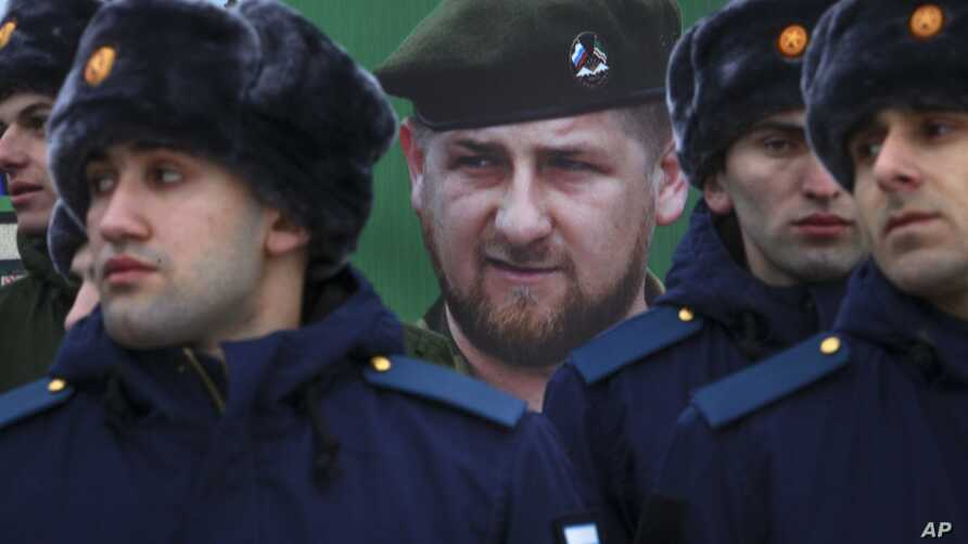 FILE - Newly-drafted Chechen conscripts, who were called to service in autumn, stand in front of a portrait of Chechen regional leader Ramzan Kadyrov as they prepare to march in Grozny, Russia, Nov. 28, 2017.