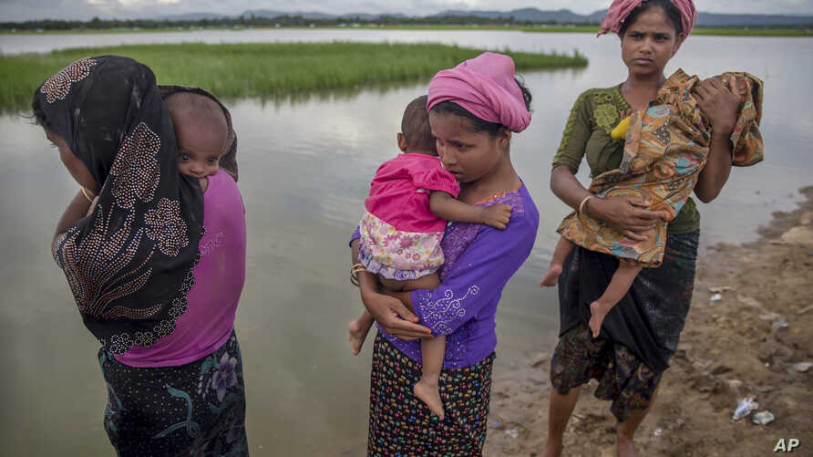 Rohingya Muslim women, who crossed over from Myanmar into Bangladesh, stand holding their sick children after Bangladesh border guard soldiers refused to let them journey towards a hospital and turned them back towards the zero line border in Palong