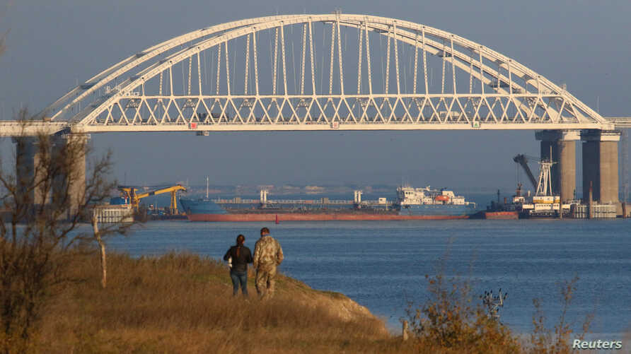 A Russian cargo ship is seen beneath a bridge connecting the Russian mainland with the Crimean Peninsula after three Ukrainian navy vessels were stopped by Russia from entering the Sea of Azov via the Kerch Strait in the Black Sea, Crimea November 25