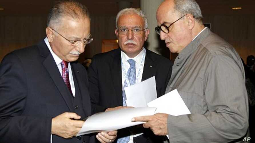Palestinian Foreign Minister Riyad al-Malki (C) stands between Organization of Islamic Cooperation Secretary General Ekmeleddin Ihsanoglu (L) and Palestinian ambassador to UNESCO Elias Sanbar (R) during the 36th session of UNESCO's General Conference