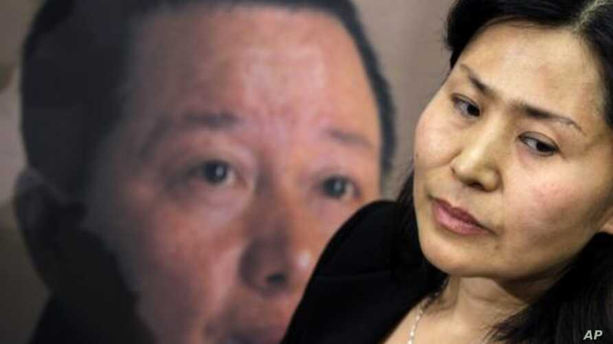 Geng He, wife of disappeared Chinese human rights lawyer Gao Zhisheng, seen on poster at rear, is interviewed before a news conference with Rep. Chris Smith, R-N.J., on Capitol Hill in Washington. (File Photo - January 18, 2011)