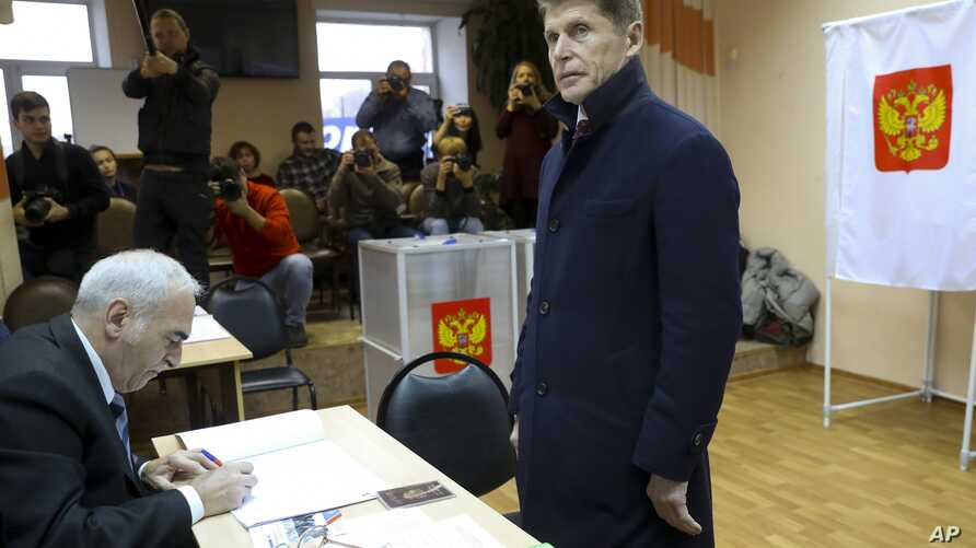 Oleg Kozhemyako, acting governor of the far eastern region of Primorsky Krai waits to get his ballot at a polling station in Vladivostok, Russia, Dec. 16, 2018.