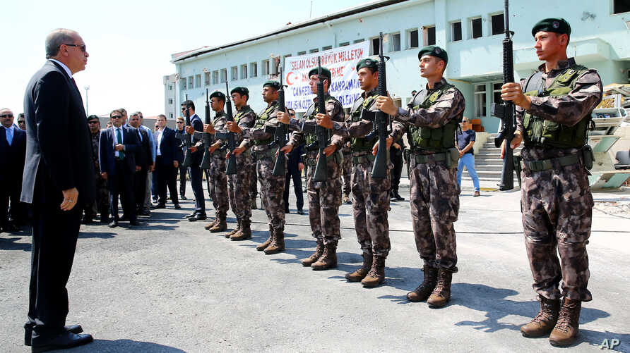 Turkey President Recep Tayyip Erdogan, left, reviews officers of the special police forces, at their headquarters in Ankara, Turkey, Friday, July 29, 2016.