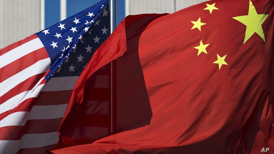 U.S. flag and China's flag flutter in winds at a hotel in Beijing, Sept. 5, 2012.