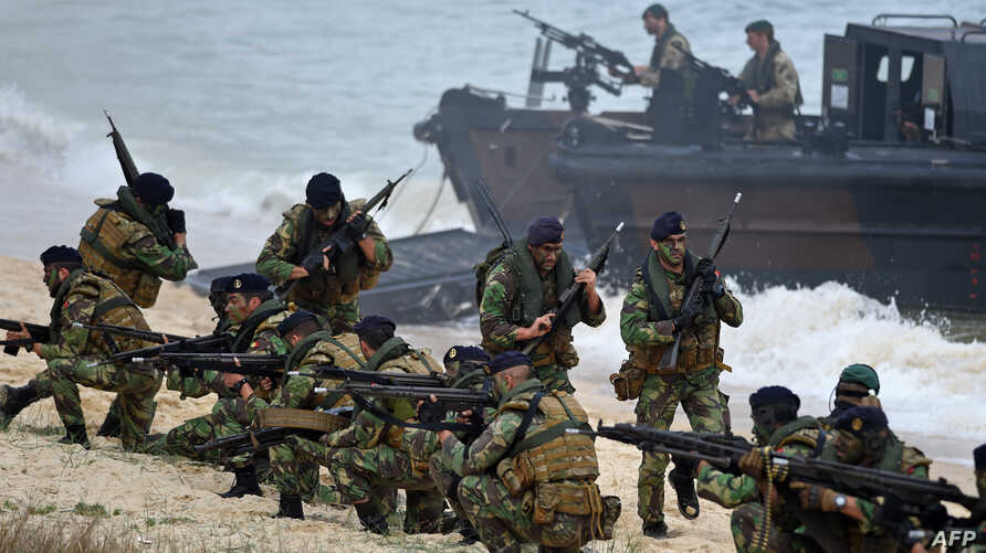 FILE - Portuguese Fuzileiros secure the area after disembarking from an amphibious transport during an exercise as part of NATO's Trident Juncture 2015 in Troia, 100 kms south of Lisbon, Nov. 5, 2015.