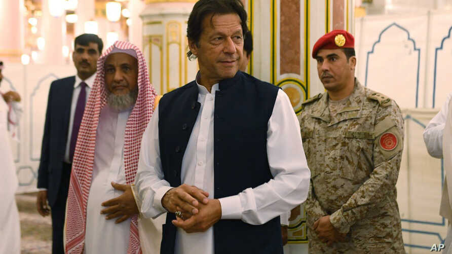 In this Tuesday, Sept. 18, 2018, photo released by the state-run Saudi Press Agency, Pakistani Prime Minister Imran Khan, center, visits the Prophet's Mosque in Medina, Saudi Arabia. Khan, a former cricketer, is on a tour of Saudi Arabia and the Unit
