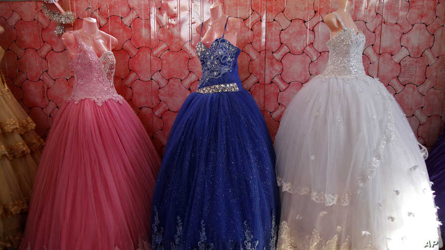 FILE - Bridal gowns and engagement dresses are displayed in a small shop in the Zaatari camp for Syrian refugees in northern Jordan, Aug. 6, 2017. Nearly 10,500 girls in Jordan were married before reaching their 18th birthdays in 2017.