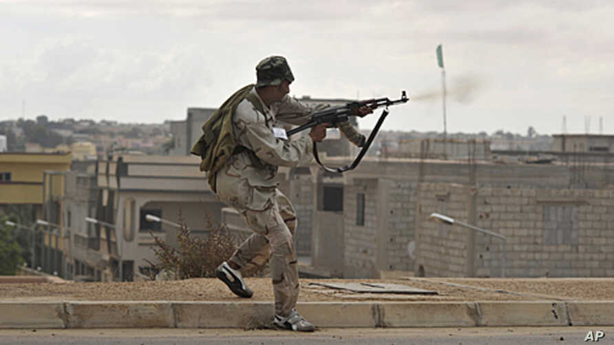 A Libyan revolutionary fighter fires his machine gun while attacking pro-Gadhafi forces on the western side of Sirte, Libya, October 13, 2011.