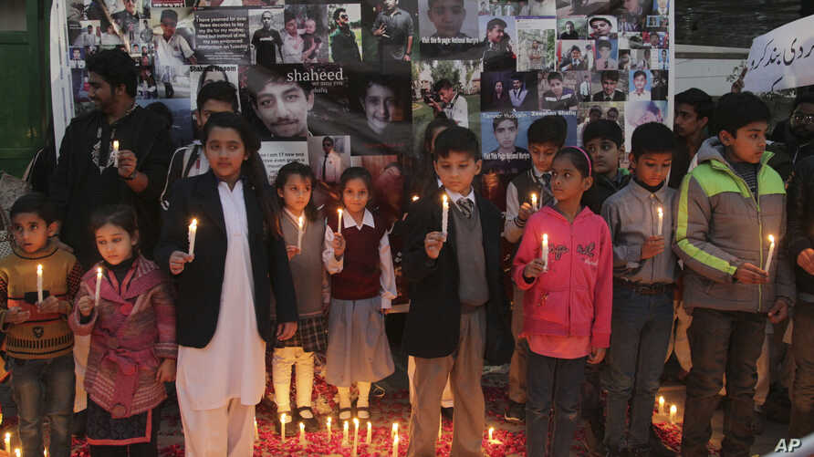 Pakistani children take part in a candle light vigil to mark second anniversary of the attack on a Peshawar school in 2014, in Lahore, Pakistan, Dec. 16, 2016.
