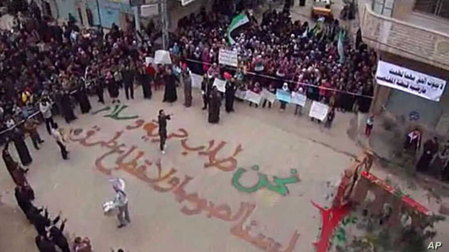 "In this image from amateur video made available by the Shaam News Network and shot on Friday, December 30, 2011, protesters gather in Homs, Syria. The writing on the ground, in Arabic, reads: ""We are those who seek freedom and peace. We are not thiev"