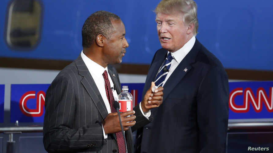 Republican U.S. presidential candidates Dr. Ben Carson and businessman Donald Trump talk during a commercial break in the Republican presidential candidates debate, Sept. 16, 2015.